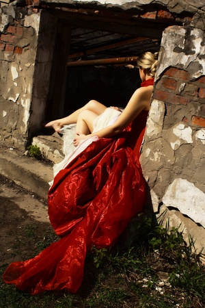 sad woman in red dress in the ruins Stock Photo