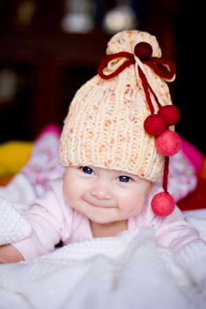 pompon: cute happy  baby girl in yellow hat with colourfu bobbles
