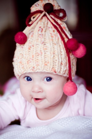 cute surprised baby girl in yellow hat with colourful bobbles