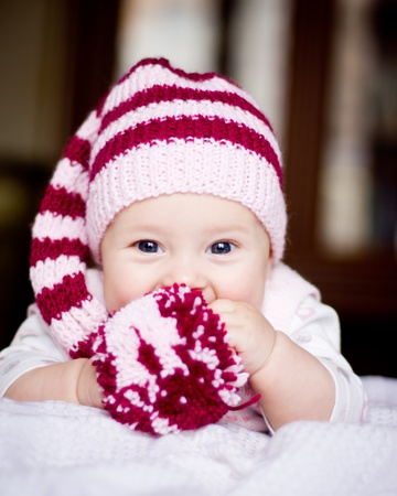 cute baby in a hat with pompom in her hands
