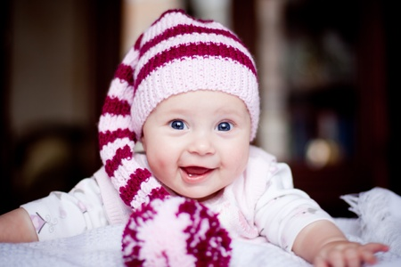 cute baby in a striped purple hat with pompom Stock Photo