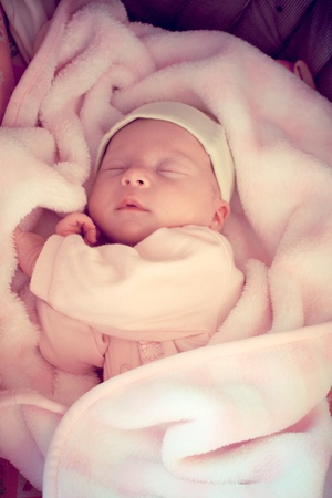 two weeks old baby sleeping in pink blanket photo