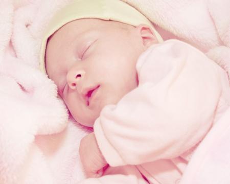two weeks old baby sleeping in pink blanket
