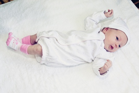 two weeks old baby girl on a white towel