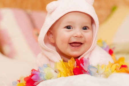 smiling baby girl in pink playing with hawaiian flower garland