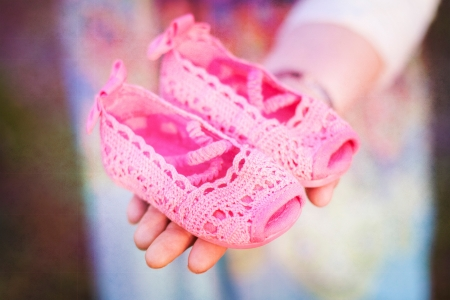 bright pink baby shoes in womans hand
