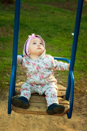 Cute little girl playing on the swings