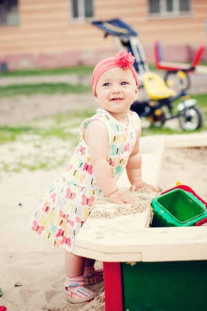 Cute baby girl playing with the sand