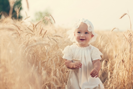 Laughing kid in sunny wheat  field in vintage dress Stock Photo