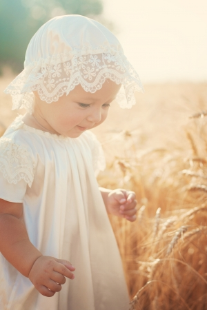 Laughing kid in sunny wheat  field in vintage dress 스톡 콘텐츠