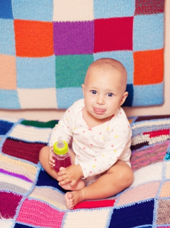 baby girl holding a bottle with juice