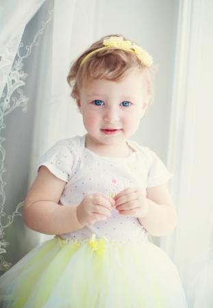 baby girl standing near the window