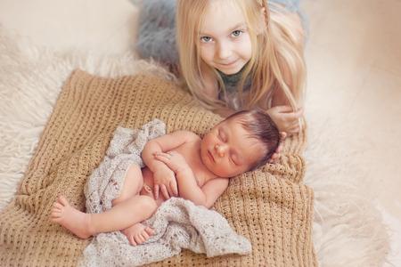 Naked girl: healthy newborn baby one week old sleeping near his older sister