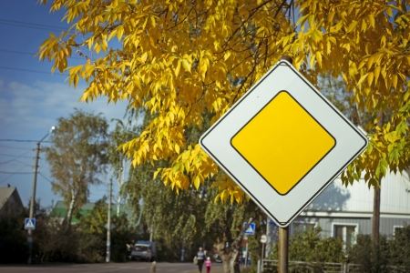 the photo of a road sign on an autumn background