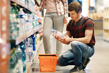 Young couple buys water at the supermarket Stock Photo