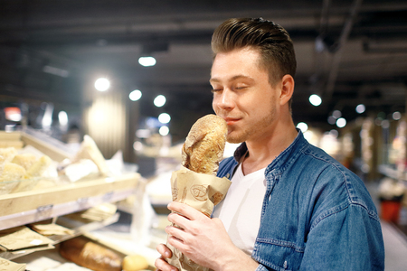 A young man chooses a bread in shop