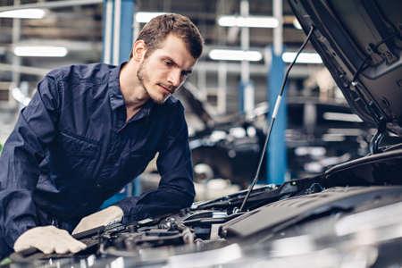 Auto car repair service center. Mechanic examining car engine