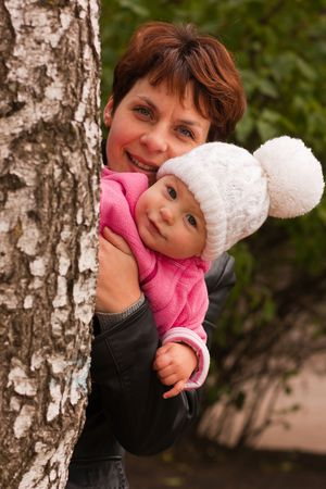 Mother holding baby girl in hands playing peek-a-boo behind the birch photo