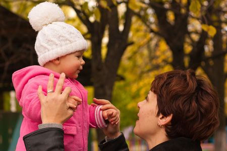 Mother holding baby girl with her hands preparing to jump against yellow autumn nature Stock Photo - 8056908