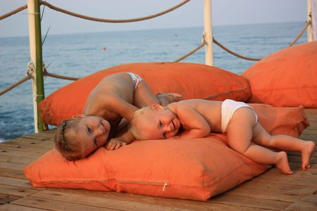 Children playing on orange pillows on pier against the sea