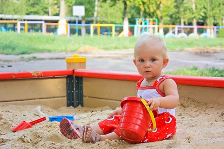 Little baby girl sitting playing in a sandbox in playground outdoor