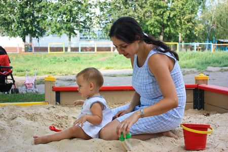 sandbox: Little baby girl with mother sitting playing in a sandbox in playground outdoor Stock Photo