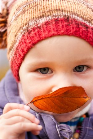 Beautiful baby with autumn leaf smiling in a funny hat outdoor against autumn nature photo