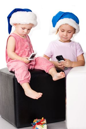 Two kids in Santa's blue hats sending greeting messages on the mobiles Stock Photo - 8272256