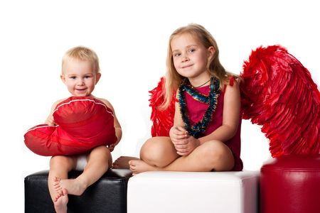 Beautiful baby with heart shaped red pillow and girl with angels red wings and tinsel photo