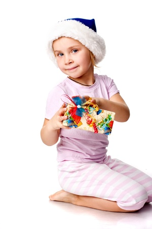 Girl in Santasblue hat holding a  present isolated on white photo