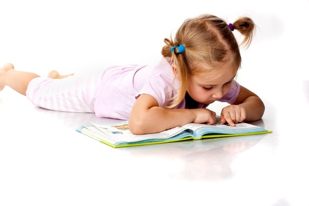 children reading books: Beautiful girl lying reading a book
