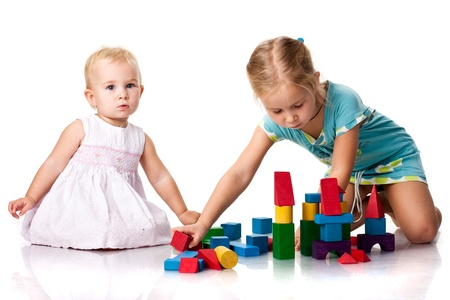 Children building a castle with cubes isolated on white photo
