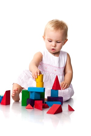 Beautiful baby building a castle with cubes isolated on white photo