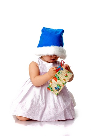Beautiful baby in Santa's hat with a present isolated on white Stock Photo - 8272291