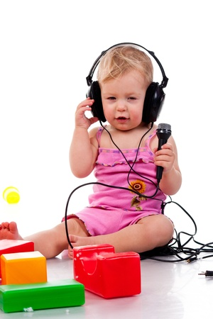 Baby with headphones and microphone, isolated on a white background photo