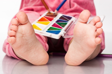Babys feet with paint and pencils isolated on white photo