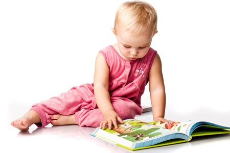 Beautiful baby girl lying reading a book