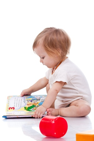 baby facial expressions: Beautiful baby girl lying reading a book