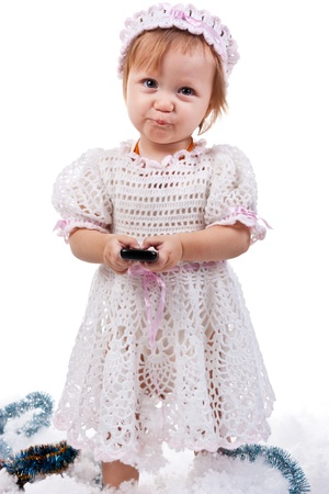 Beautiful baby with a mobile phone isolated on white photo