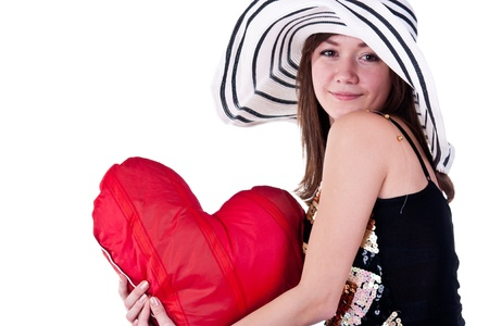 Beautiful young girl sitting on a bar chair with red heart pillow  isolated on white photo