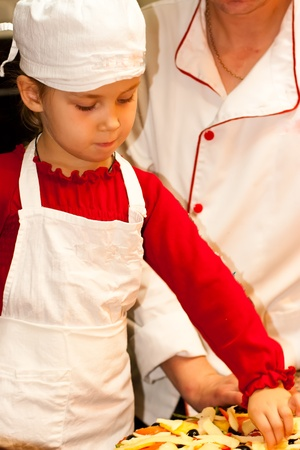 Beautiful girl cooking in a hat and apron photo