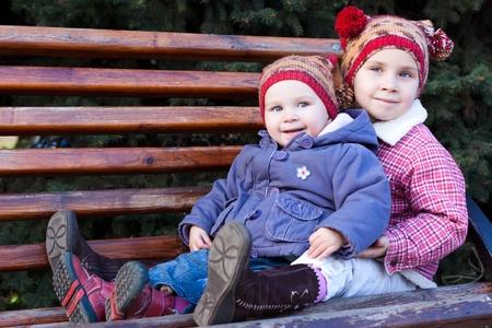Ni�os sentados en un banco al aire libre  Foto de archivo - 8565137