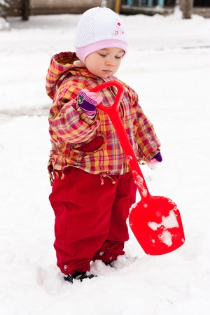 Child playing with spade in snow in winter photo