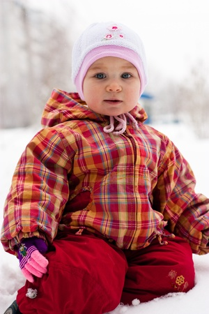 Beautiful girl playing outdoor in snow in winter photo