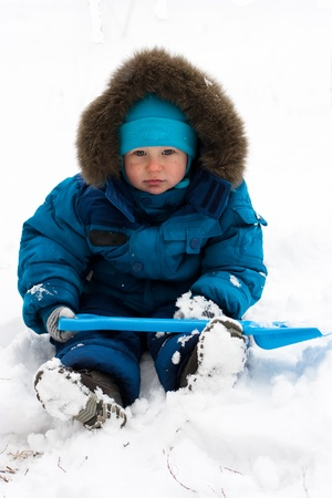 Cute boy playing outdoor in snow in winter photo