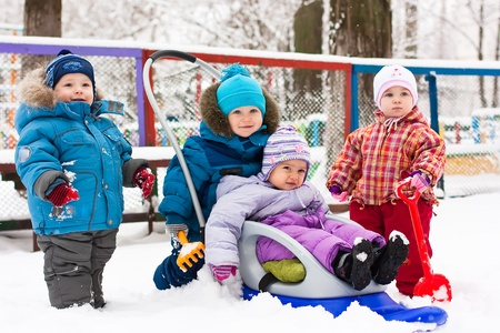 Children playing in snow outdoor in winter photo