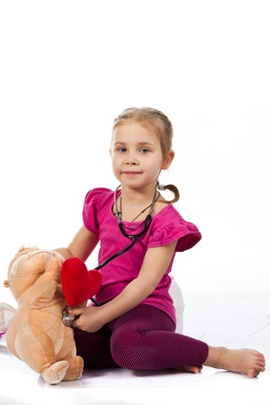 doctor toys: Beautiful girl playing doctor with a doll isolated on white