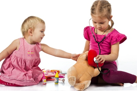 Children playing doctor with a doll isolated on white
