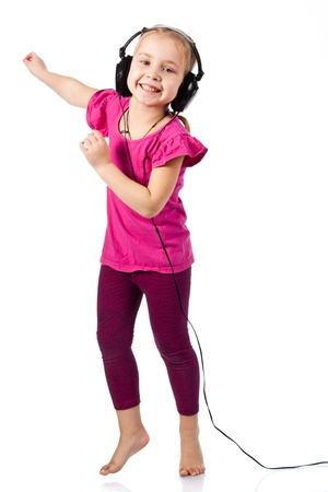 Beautiful girl in headphonesdancing to the music isolated on white photo