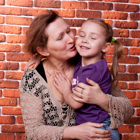 Grandmother kissing her grand daughter against brick wall photo